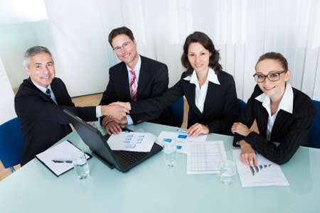 hardworking: Business colleagues seated around a table in a meeting congratulating one another by shaking hands