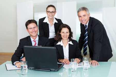 Confident successful business team of diverse executives posing in an office together smiling happily at the camera photo