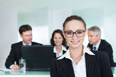 advancement: Corporate advancement and leadership concept with a confident smiling attractive businesswoman wearing glasses standing with her arms folded Stock Photo