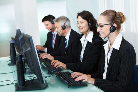 com: Line of professional stylish call centre operators wearing headsets seated behind their computers giving assistance