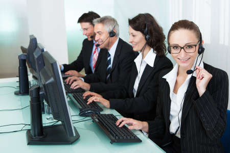 Line of professional stylish call centre operators wearing headsets seated behind their computers giving assistance photo