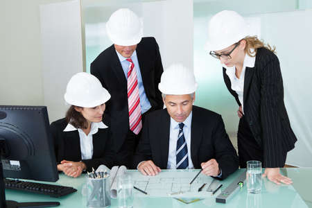 Meeting of four diverse architects or structural engineers in hardhats and suits seated in an office photo