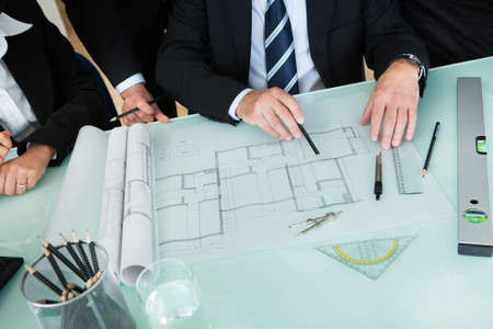 Cropped high angle view of the hands of a group of architects discussing a blueprint or architectural drawing laid out on a tabletop photo