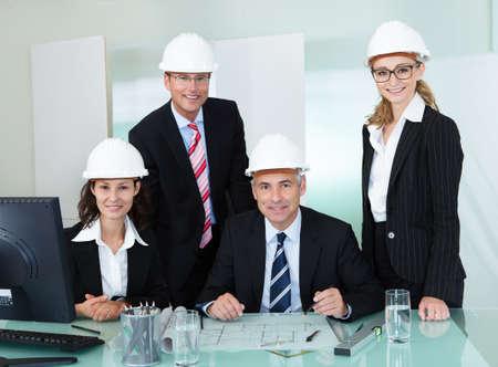 Four diverse professional partners in an architectural firm posing behind a table in an office wearing their hardhats and suits photo