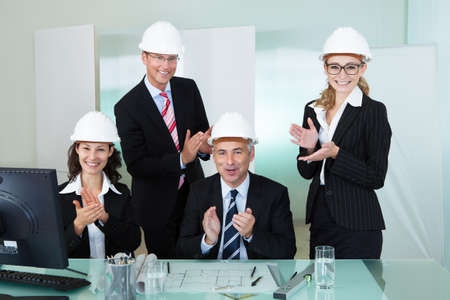 structural engineers: Team of four diverse architects or structural engineers wearing hardhats in an office applauding