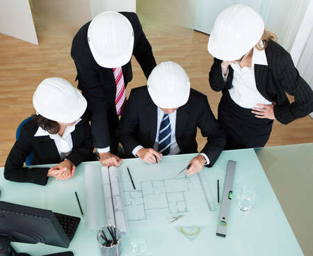 hardworking: Overhead view of a group of architects or structural engineers discussing a blueprint laid out on the table in front of them