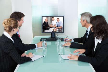conferentie: Groep van mannelijke en vrouwelijke ondernemers zittend aan een tafel te kijken naar een online presentatie op een computerscherm