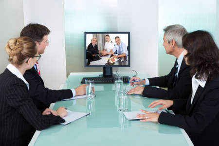 Group of male and female businesspeople seated at a table watching an online presentation on a computer screen photo
