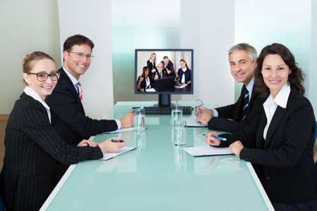 training programs: Group of male and female businesspeople seated at a table watching an online presentation on a computer screen