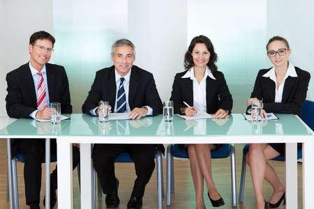 entrevista: Grupo de oficiales de personal corporativo sentado en una mesa