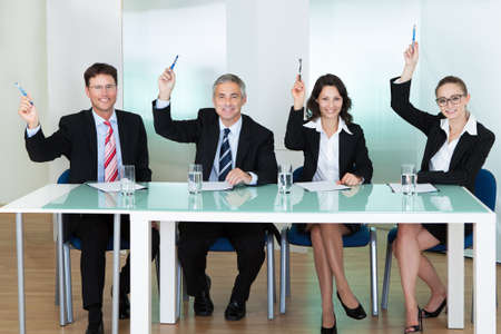 hunters: Group of corporate recruitment officers interviewing for a professional vacancy raising their pens Stock Photo