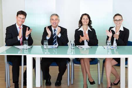 jurado: Grupo de los oficiales de reclutamiento corporativo entrevista para un puesto vacante profesional aplaudiendo Foto de archivo