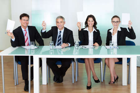 jurors: Group of four stylish professional judges seated at a long table holding up blank cards for their scores