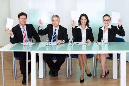 jurado: Grupo de cuatro jueces profesionales elegantes sentados en una larga mesa que soporta tarjetas en blanco para sus puntuaciones