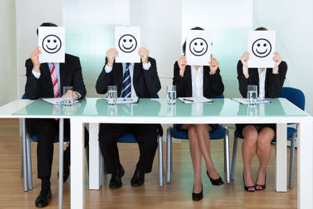 jurors: Row of business executives with smiley faces in front of their faces Stock Photo