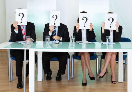 queries: Row of businesspeople with question marks signs in front of their faces