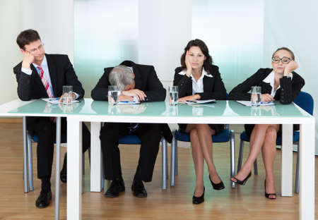 bored man: Bored panel of professional judges or corporate interviewers lounging around on a table napping as they wait for something to happen Stock Photo