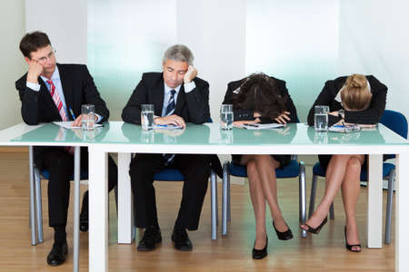 tedious: Bored panel of professional judges or corporate interviewers lounging around on a table napping as they wait for something to happen Stock Photo