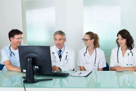 healthcare office: Doctors having a meeting seated at a table in front of a computer discussing case histories Stock Photo