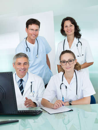 comprising: Medical team comprising male and female doctors posing together in an office smiling at the camera