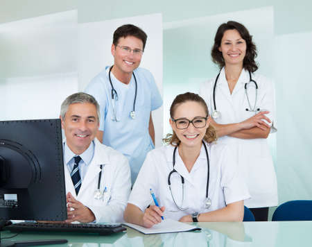 medical team: Medical team comprising male and female doctors posing together in an office smiling at the camera