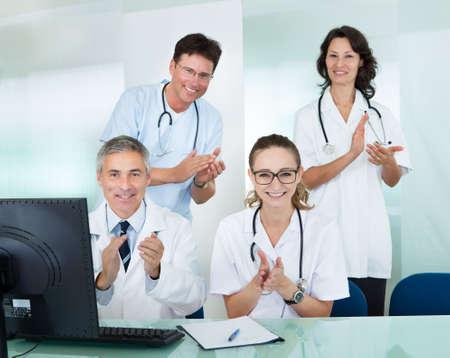 aplaudiendo: Feliz equipo médico que comprende médicos y médicas con una amplia sonrisa y dando un pulgar hacia arriba de éxito y esperanza Foto de archivo