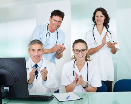 Happy medical team comprising male and female doctors smiling broadly and giving a thumbs up of success and hope photo