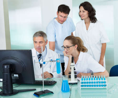 Paramedical or technical staff grouped together looking at a computer in a laboratory photo