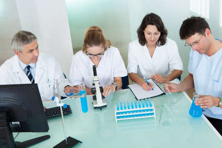 paramedical: Paramedical or technical staff grouped together looking at a computer in a laboratory Stock Photo