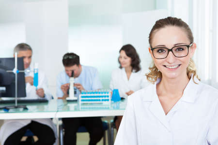 residents: Attractive smiling female lab technician or technologist wearing glasses standing in the foreground