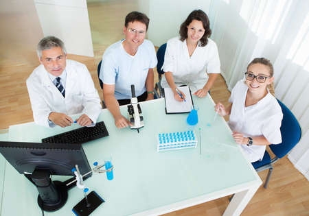 residents: Overhead view of four laboratory technicians at work seated around a table reading and recording tests on a microscope and computer Stock Photo