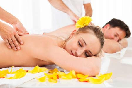 masaje deportivo: Atractiva pareja acostado al lado del otro en un balneario disfrutando del lujo de un masaje de tejido profundo de nuevo juntos Foto de archivo