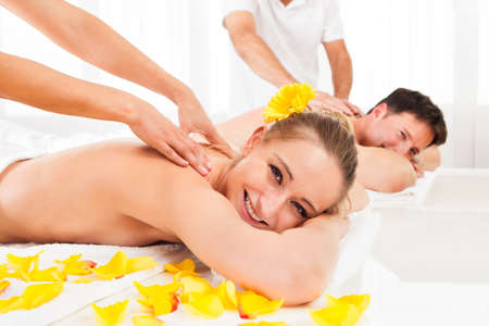 getting married: Attractive couple lying side by side in a spa enjoying the luxury of a deep tissue back massage together