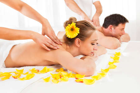 sports massage: Atractiva pareja acostado al lado del otro en un balneario disfrutando del lujo de un masaje de tejido profundo de nuevo juntos Foto de archivo