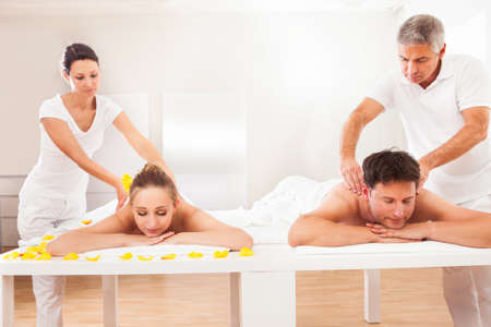 Professional masseurs in a spa giving back massages to an attractive husband and wife lying side by side photo