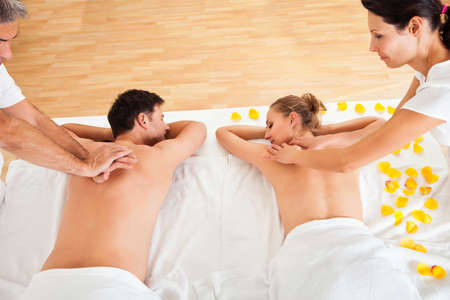 getting together: Young couple relaxing and enjoying a joint back massage at a spa and the woman is surrounded by yellow flower petals Stock Photo