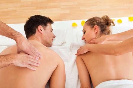 sports massage: Joven pareja relajarse y disfrutar de un masaje en la espalda conjunta en un balneario y la mujer est� rodeada de p�talos de flores amarillas