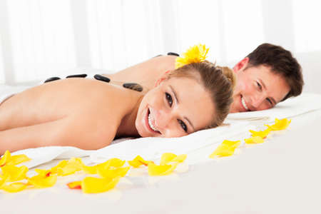 massage stones: Couple having a hot stone massage treatment in a spa relaxing as the heat from the stones relaxes their muscles Stock Photo