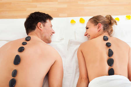 therapeutical: Couple enjoying a hot stone massage in a spa where heated stones are placed along the spine to relax the muscles Stock Photo