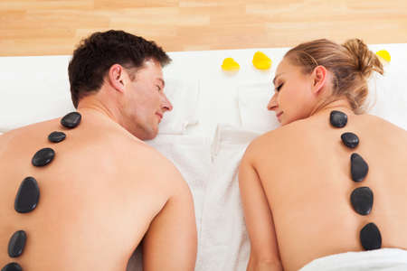 hot rock therapy: Couple enjoying a hot stone massage in a spa where heated stones are placed along the spine to relax the muscles Stock Photo