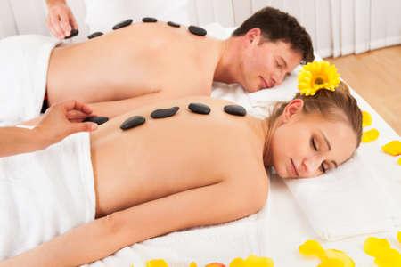day spa: Couple having a hot stone massage treatment in a spa relaxing as the heat from the stones relaxes their muscles Stock Photo