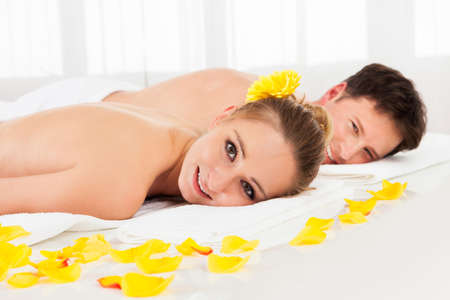 Smiling relaxed couple lying side by side on a table amongst yellow flowers at a spa with their top half bare and a towel around their loins photo