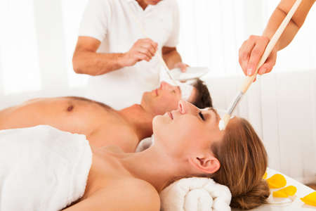 Young couple lying side by side in a spa with beauticians applying a face mask to them both photo