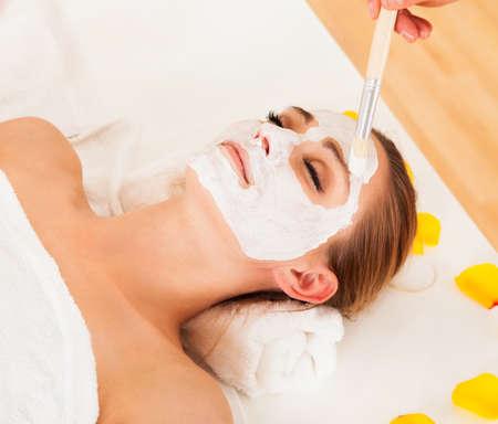levantandose: Terapeuta de la aplicación de una máscara facial a la cara de una joven y bella mujer rubia con un cepillo cosmética