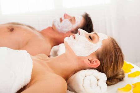 tratamiento facial: Hombre y mujer en máscaras faciales recostado sobre toallas blancas limpias en un spa relajante