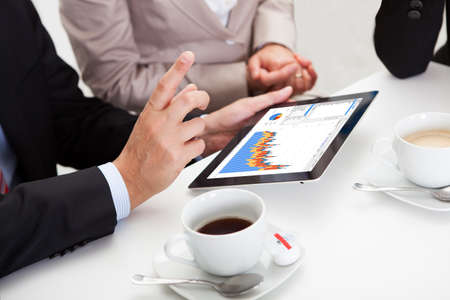 Business colleagues enjoying a coffee break smiling at something on the screen of a tablet held by one of the men Stock Photo - 17277298