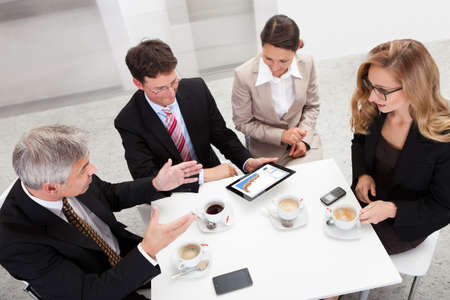 Business colleagues enjoying a coffee break smiling at something on the screen of a tablet held by one of the men photo