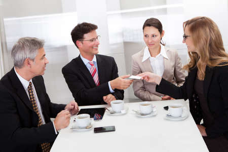 businesswoman card: Businesspeople exchanging cards over coffee while having an informal meeting in a cafe Stock Photo