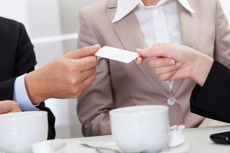 Businesspeople exchanging cards over coffee while having an informal meeting in a cafe Imagens