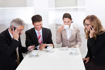 lunch meeting: Business executives sitting around a table enjoying a relaxing cup of coffee together during a break Stock Photo